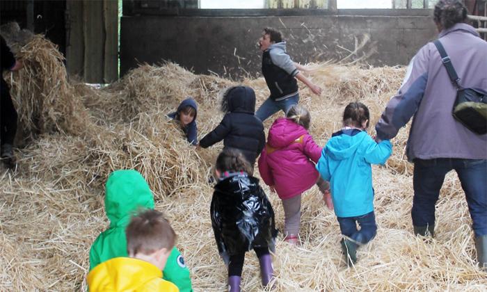 Des enfants jouent dans la paille pour un anniversaire à la ferme du Gazenas